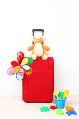 Red suitcase with toy flower and child toys isolated on white