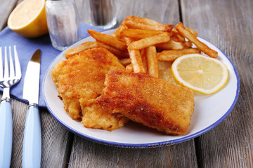 Breaded fried fish fillets and potatoes with with sliced lemon