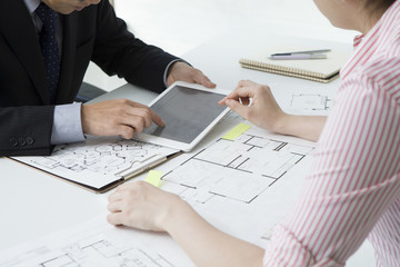 Businessman is showing the floor plan with electronic tablet