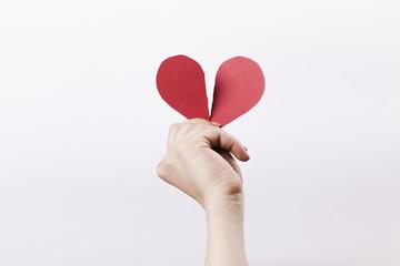 Woman hand holding broken paper heart