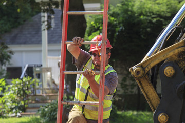 Construction worker removing ladder from shoring