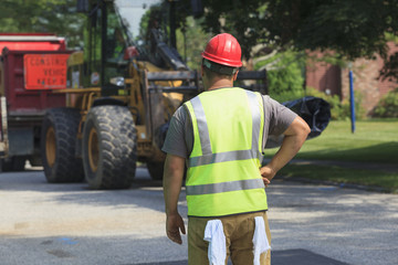 Construction worker watching front end loader