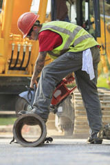 Construction worker cutting water main with gas powered saw