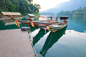 Long-tail boat and lakeside raft houses on Cheow Lan Lake, Khao