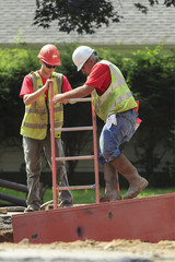 Construction workers descend into shoring using ladder