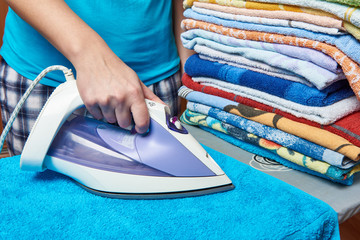 Woman housewife ironing towels