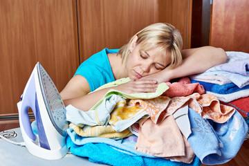 Tired housewife sleeping on an ironing board