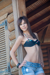 Lady with top bikini and jean short in wooden cabin
