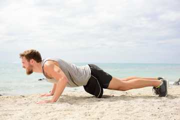 Push-ups - man fitness exercising on beach