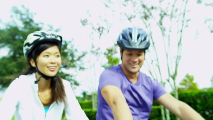 Happy Ethnic Couple Activity Cycling Together Outdoors