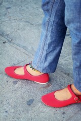 A woman wearing red shoes with jeans