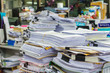 Pile of documents on desk stack up high waiting to be managed. - 77043765