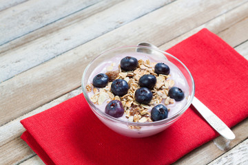 Yogurt with blueberries and muesli on wooden background