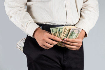 Man with abundant of money in his pockets, counting some cash