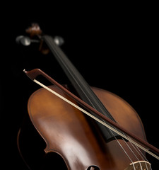Cello and its bow set against a black background.