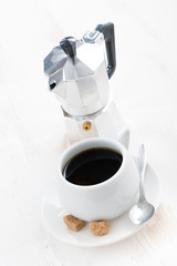 cup of black coffee and coffeemaker, vertical