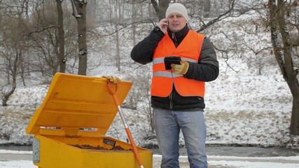 Worker talking on the cell phone near the sandbox in winter