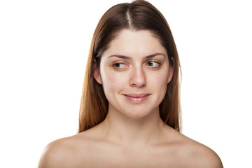 Sceptical young woman without make up on white background
