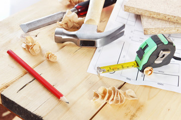 Working tools of carpenter lie on the wooden workbench