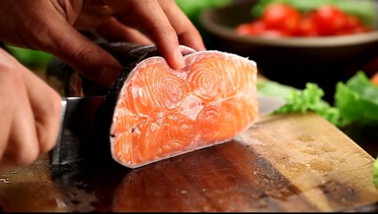 Male hands cutting salmon fish.