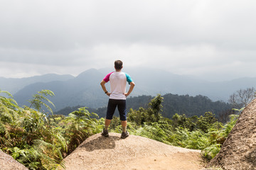 Man standing on the peak of a tropical highland forrest