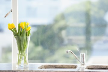 Yellow flower in a vase on the sink