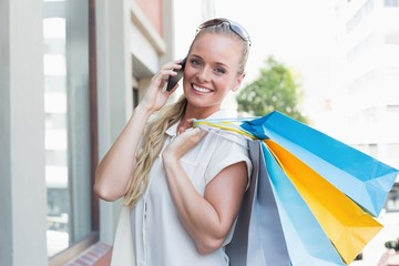 Pretty blonde making a call and holding shopping bags