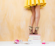 Woman in yellow dress standing on pile of books