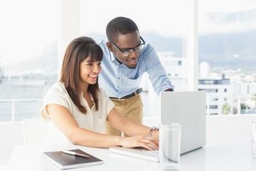 Smiling team using laptop together