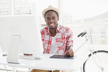 Smiling businessman in straw hat using digitizer