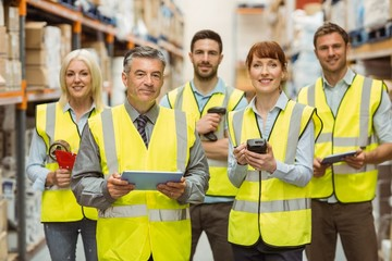 Smiling warehouse team looking at camera