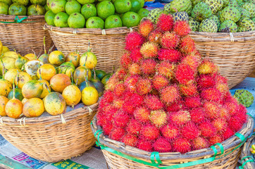 Street market with tropical fruit: rambutan, passion fruit