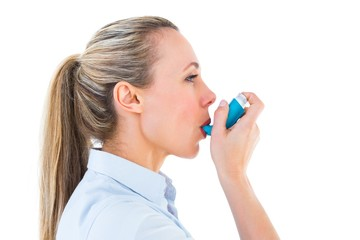 Pretty blonde using an asthma inhaler