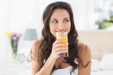 Happy brunette having glass of orange