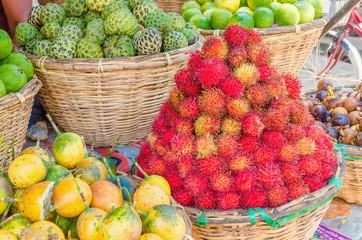 Baskets at a street market full of tropical fruit: rambutan
