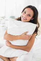 Smiling brunette sitting on bed