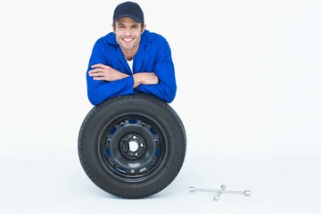 Handsome mechanic leaning on tire