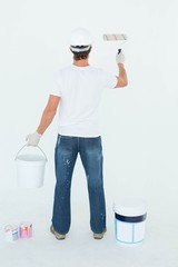 Rear view of man using paint roller