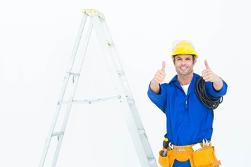 Happy electrician gesturing thumbs up by ladder