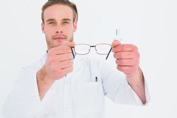 A optician showing glasses next to an eye test