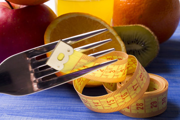 Fruits with measuring tape with wood background