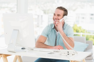 Smiling businessman on the phone while using computer