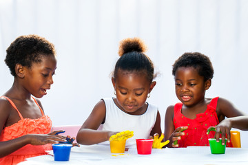 Three African kids painting together with hands.