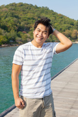 portrait of young asian man standing on wood pier with relaxing