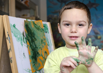 Portrait of a child boy  painting a colorful abstract picture.