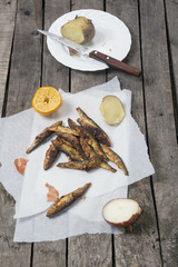 Fried smelt with lemon, onion and potato
