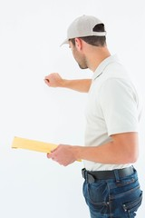 Delivery man with envelop knocking on white background