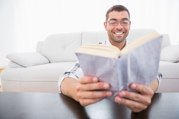 A smiling man reading a book