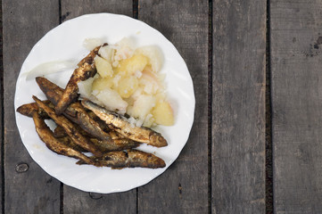 Fried smelts with potato salad on plate