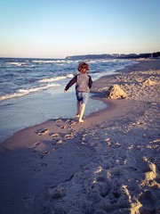 child running on the beach at sunset